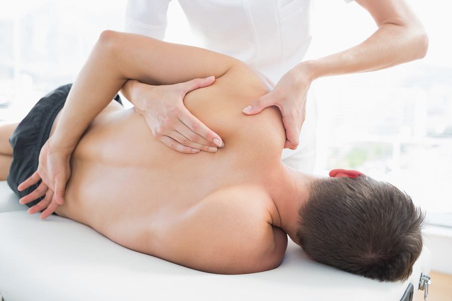 Professional female osteopath giving shoulder massage to a patient